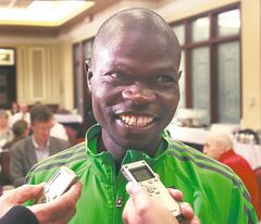Thomas  Omwenga talks to reporters after his  marathon win.