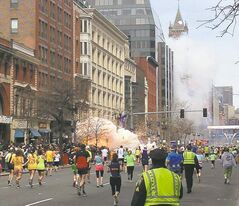 Runners head toward the finish line of the Boston Marathon Monday as an explosion erupts.