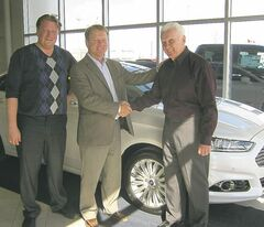 Mid-Town Ford President Rob Fridfinnson (centre) congratulates first local Ford Fusion Energi Hybrid owner Peter Johnson. Sales rep Sam Melquits is at left.