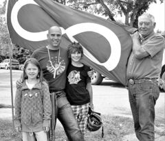 Irvin Goodon, with son Will, grandchildren Taylor (left), Hunter and Métis flag.