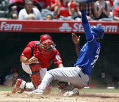 Kansas City Royals' Pedro Ciriaco, right, eludes the tag by Los Angeles Angels catcher Chris Iannetta to score on a sacrifice fly in the third inning of a baseball game on Sunday, May 25, 2014, in Anaheim, Calif. Royals' Eric Hosmer hit the fly ball to left field for the out in foul territory. (AP Photo/Alex Gallardo)