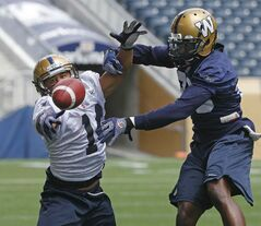 Bruce Johnson knocks down a pass intended for Aaron Woods today during the Bomber practice.