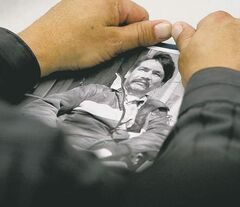 A family member holds a portrait of Brian Sinclair.
