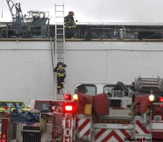 Firefighters climb to the roof of Maple Leaf Foods at Lagimodiere Boulevard and Marion Street Wednesday afternoon after a fire was reported.