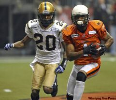 BC Lions Arland Bruce (right) runs for a touchdown, trailed by Winnipeg Blue Bombers Deon Beasley during second-half action of the 2011 Grey Cup final between the Winnipeg Blue Bombers and the BC Lions in Vancouver November 27, 2011.