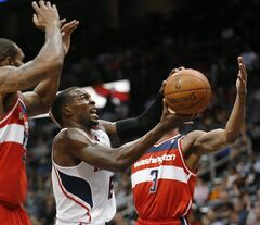 Atlanta Hawks guard Shelvin Mack (8) drives against Washington Wizards guard Bradley Beal (3) during the first half of an NBA basketball basketball game Wednesday, Feb. 19, 2014, in Atlanta. (AP Photo/John Bazemore)