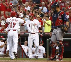 Cincinnati Reds' Kris Negron (17) is congratulated by Zack Cozart (2) after Negron hit a two run home run off Cleveland Indians starting pitcher Danny Salazar in the fourth inning of a baseball game, Wednesday, Aug. 6, 2014, in Cincinnati. Indians catcher Yan Gomes watches at right. (AP Photo/David Kohl)