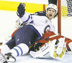 Winnipeg forward Jim Slater pins down Calgary Flames goalie Miikka Kiprusoff during second-period action in Calgary Friday night.