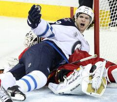 Calgary Flames goalie Miikka Kiprusoff lies under the Winnipeg Jets' Jim Slater during second-period action at the Scotiabank Saddledome in Calgary Friday. The Flames won 5-3.