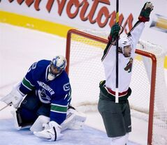 Vancouver Canucks goalie Roberto Luongo (1) looks on as Minnesota Wild center Matt Cullen (7) celebrates his goal during third period NHL hockey action at Rogers Arena in Vancouver, B.C. Monday, March,18, 2013. THE CANADIAN PRESS/Jonathan Hayward