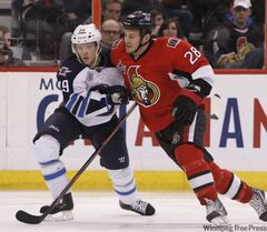 Zenon Konopka (R) of the Ottawa Senators is held by Tobias Enstrom (penalty on the play) of the Winnipeg Jets during the third period of NHL action in Ottawa Monday.