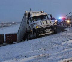 A towtruck pulls a semi-trailer up an incline after it was hit by a train this morning. The southbound semi went off the east Perimeter Highway near Gunn Road and ended up on rail tracks. The train's trailer was then struck by the train.