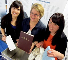 (L-R) Sarah, Vivian, and Stephanie Painter add a speech, a thesis, and some stylish shoes and scrub dress from the late 80's early 90's, to the College of Manitoba Nurses' Time capsule.