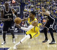Indiana Pacers forward Paul George, center, slips as he cuts between Brooklyn Nets forward Kevin Garnett, left, and guard Shaun Livingston in the second half of an NBA basketball game in Indianapolis, Saturday, Feb. 1, 2014. The Pacers defeated the Nets 97-96. (AP Photo/Michael Conroy)
