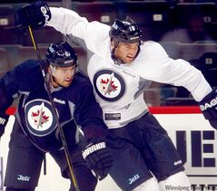 Jets captain Andrew Ladd (right) gets tangled up with Ron Hainsey at practice Wednesday. Ladd and Dustin Byfuglien return to Chicago tonight for the first time in 17 months.