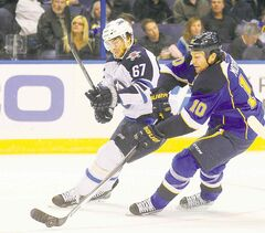 Brenden Morrow of the Blues and the Jets' Michael Frolik battle for the puck Tuesday night.