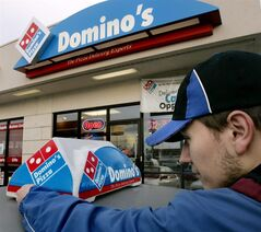 FILE - In this Feb. 21, 2007 file photo, Domino's Pizza delivery person Brandon Christensen plugs in the company sign atop his car in Sandy, Utah. The pizza delivery chain on Monday, June 16, 2014 plans to introduce a function on its mobile app that lets customers place orders by speaking with a computer-generated voice named