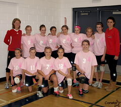 The Grade 8 girls' volleyball team at Charleswood School poses for a team photo in their pink jerseys along with U of W coach Diane Scott and Wesmen player Ozana Nikolic.