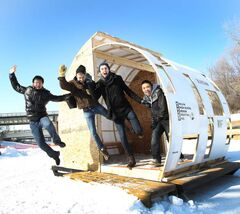 Kelvin High School students jump out of their warming hut that they designed and built for The Forks river Trail.