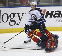 Florida Panthers' Mike Weaver (43) tries to slow Winnipeg Jets' Spencer Machacek (46) during the second period of an NHL hockey game in Sunrise, Fla., on Tuesday.