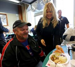 Donna D'Errico, who once starred on Baywatch, serves a Thanksgiving meal to Joe Richard at Siloam Mission.