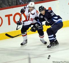 The Winnipeg Jets' Mark Flood (33) and Washington Capitals'  Marcus Johansson fight for possession in the Jets' end of the rink Thursday at the MTS Centre.