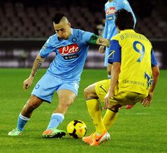 Napoli's Marek Hamsik, left, faces Chievo Verona's Simone Bentivoglio, during a Serie A soccer match, at the San Paolo stadium in Naples, Italy, Saturday, Jan. 25, 2014. (AP Photo/Salvatore Laporta)