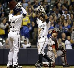 Milwaukee Brewers' Jean Segura celebrates with Carlos Gomez in front of Arizona Diamondbacks catcher Miguel Montero after Segura hit a two-run home run during the sixth inning of a baseball game Monday, May 5, 2014, in Milwaukee. (AP Photo/Morry Gash)