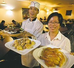 Guang Han Wu (L), owner/chef, and Mei Zhi Yang with Braised Eggplant With Soy On Sizzling Iron, Walnut Shrimp and Hakga Special Salted Chicken at the Huang Pu River restaurant.
