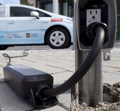 A power cable runs from an electrical outlet to recharge an electric vehicle in downtown Vancouver, B.C. Tuesday, Sept. 14, 2010. Ontario's overabundance of utility firms may pose a major roadblock to the province's plan to boost electric car ownership, some experts say. THE CANADIAN PRESS/Jonathan Hayward