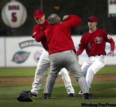 Fargo-Moorehead manager Doug Simunic aims a right roundhouse at Goldeyes hitting coach Tom Vaith Monday night as tempers boiled over in a lopsided first half at Canwest Stadium.