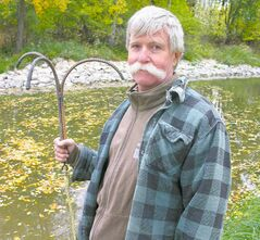 In this fall 2012 photo, Save Our Seine member Chris Pearce is pictured by the Seine River with a grappling hook. Pearce had co-ordinated the Save Our Seine Green Team's summer cleanup operation.