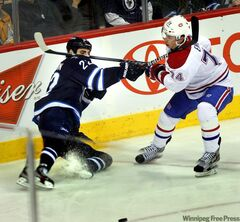 Winnipeg Jets' Chris Thorburn goes down in the corner and delivers a stick to the face and neck of Montreal Canadiens' Alexei Emelin during second-period action Thursday at the MTS Centre. Thorburn drew a high-sticking four-minute penalty on the play.