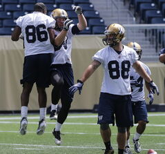 Dare we say it? The Blue Bombers are actually having fun this season. Brett Carter (centre) celebrates at TD at practice Tuesday.