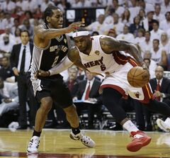 Miami Heat forward LeBron James (6) dribbles the ball as San Antonio Spurs forward Kawhi Leonard (2) defends, during the second half in Game 4 of the NBA basketball finals, Thursday, June 12, 2014, in Miami. (AP Photo/Lynne Sladky)