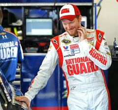 Driver Dale Earnhardt Jr. stands by his car in the garage before practice for the NASCAR Sprint Unlimited auto race at Daytona International Speedway in Daytona Beach, Fla., Friday, Feb. 14, 2014. (AP Photo/Terry Renna)