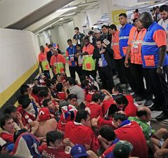 Chilean fans are surrounded by security personnel after breaking into Maracana Stadium before the group B World Cup soccer match between Spain and Chile in Rio de Janeiro, Brazil, Wednesday, June 18, 2014. (AP Photo/Bernat Armangue)