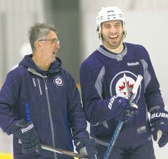 Winnipeg Jets forward Chris Thorburn has a laugh with coach Claude Noel at practice Monday.