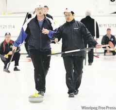 Deaf curlers David Joseph (left) and Damian Hum comment with hand signals on their rock's progress on the opening day of the 2009 MCA Bonspiel Thursday.