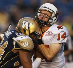 Winnipeg Blue Bomber Kenny Manor (left) runs into B.C. Lions quarterback Travis Lulay with a late hit during second-quarter CFL action at Canad Inns Stadium Friday night. He was penalized with roughing the passer.