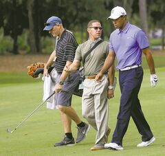 Tiger Woods walks with his caddie, Joe LaCava (left), and golfing coach Sean Foley during practice rounds Tuesday for the Players Championship tournament at TPC Sawgrass in Ponte Vedra Beach, Fla.