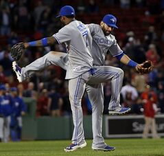 Toronto Blue Jays shortstop Jose Reyes (7) and right fielder Jose Bautista, right, celebrate their 7-4 victory over the Boston Red Sox in a baseball game at Fenway Park in Boston, Tuesday, May 20, 2014. (AP Photo/Elise Amendola)