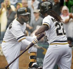 Pittsburgh Pirates' Josh Harrison, left, celebrates with teammate Andrew McCutchen after hitting a solo home run off Cincinnati Reds starting pitcher Johnny Cueto during the first inning of a baseball game in Pittsburgh, Sunday, Aug. 31, 2014. (AP Photo/Gene J. Puskar)