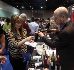 Wine festival attendees juggle glasses and programs as they sample from the more than 500 wines on offer.
