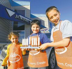 Mussie Altein 6, Ezra Cohen, 8, and Chaim Yitzchok, 10, with a menorah they made. Home Depot is holding another another workshop for kids Nov. 24.
