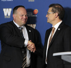 New Winnipeg Blue Bomber acting CEO Wade Miller, left, shakes the hand of board chair Brock Bulbuck this morning.