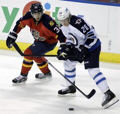 Winnipeg Jets' Antti Miettinen (20), of Finland, and Florida Panthers' Kris Versteeg (32) battle for the puck during the first period of an NHL hockey game, Friday, March 8, 2013, in Sunrise, Fla. (AP Photo/Luis M. Alvarez)