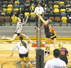 U of M's Ashley Voth (left) and U of W's Alixandra Krahn joust at the net Friday.