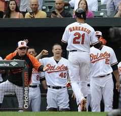 Baltimore Orioles manager Buck Showalter, left, congratulates Nick Markakis after hitting a solo home run against the Seattle Mariners in the first inning of a baseball game Sunday, Aug. 3, 2014, in Baltimore.(AP Photo/Gail Burton)