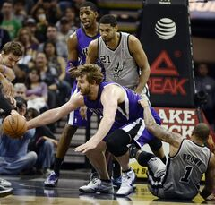 Sacramento Kings center Aaron Gray, center front, dives after the loose ball between San Antonio Spurs guard Shannon Brown, right, and Spurs forward Tim Duncan, as Kings forward Jason Thompson looks on, during the first half of an NBA basketball game, Saturday, Feb. 1, 2014, in San Antonio. (AP Photo/Darren Abate)